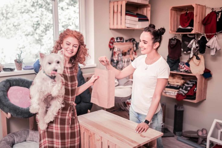 Curly red-haired woman feeling happy after shopping in pet shop.