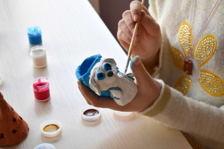 Making toys, paints a pottery clay dog figure with gouache.