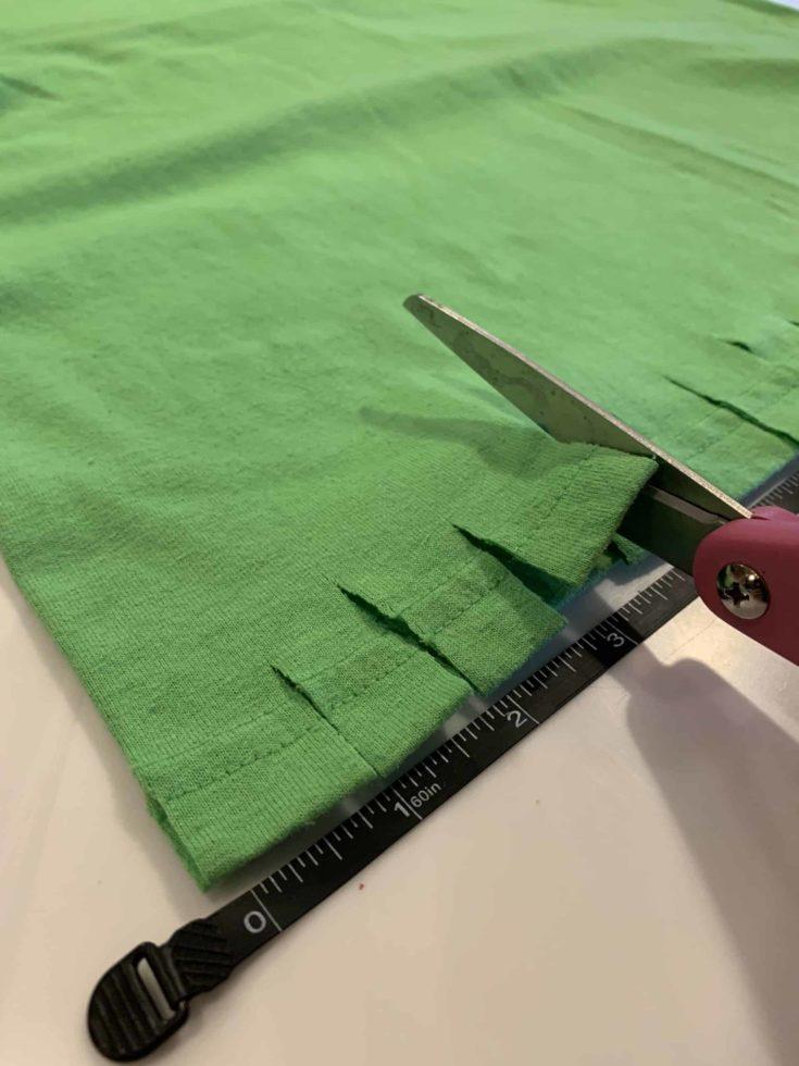 Cutting green cloth with scissor