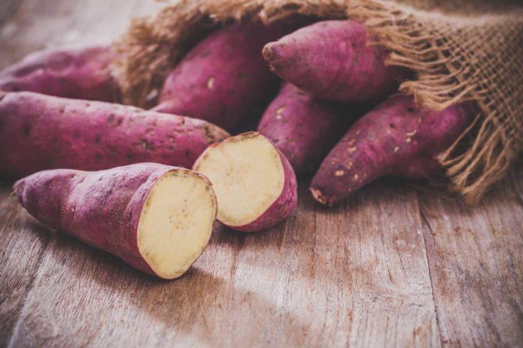 Raw sweet potatoes on wood background
