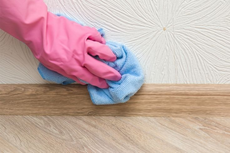 Hand in pink protective glove cleaning baseboard on the wooden floor from dust with rag at the wall. Early spring cleaning or regular clean up. Maid cleans house.
